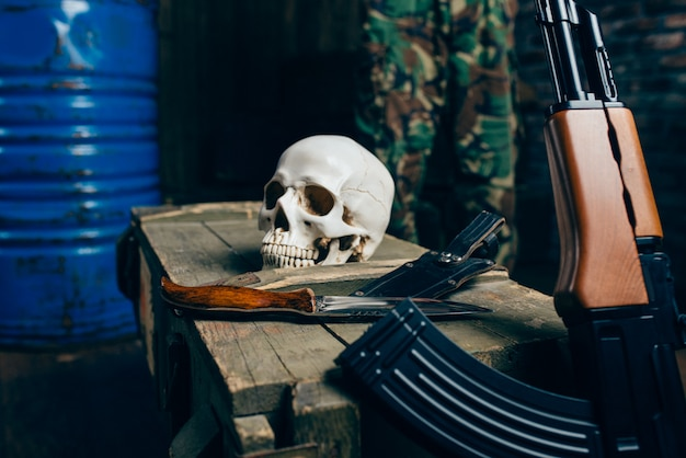Skull, bomb, knife and rifle on box of ammunition