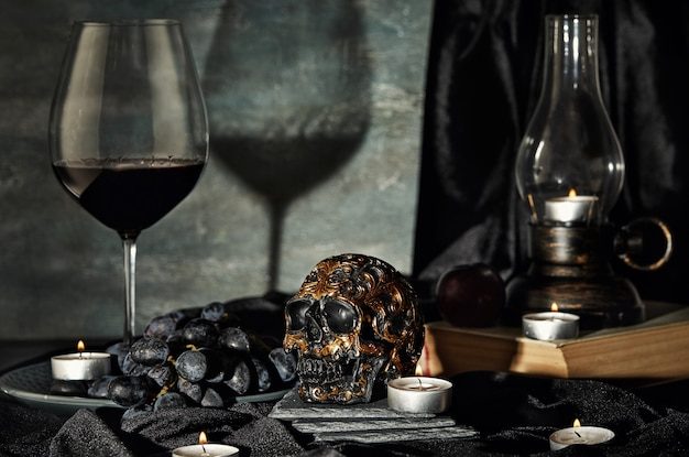 Skull, candles, wine, grapes, old lamp on a dark . halloween