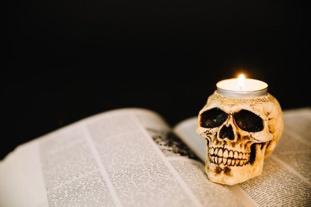 Skull candlestick and opened book