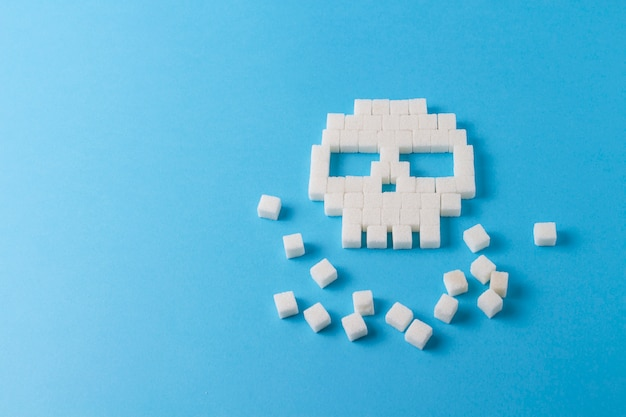 Skull of cubes of sugar and pieces of sugar on a blue background. concept sugar kills and harm sweet on the human body.