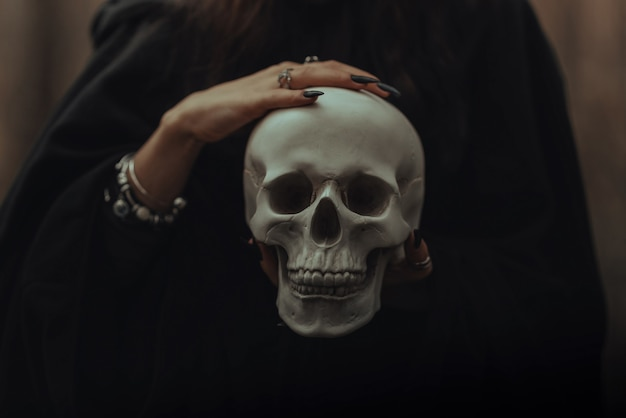 Skull of a dead man in the hands of a witch witch in a black costume for an occult satanic ritual