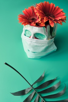 Skull in face mask with coral color gerbera flowers. dia de los muertos during pandemic.