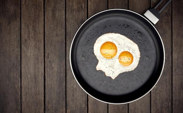 Skull fried egg on skillet on wooden