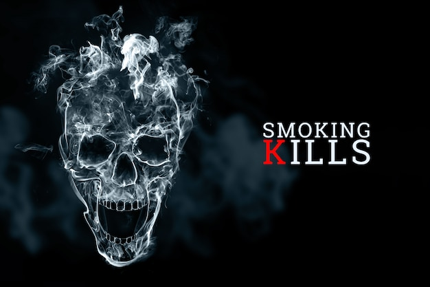 Skull from cigarette smoke on a black background. the inscription smoking kills.