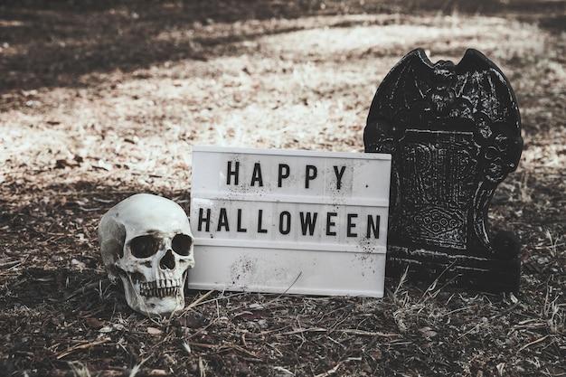 Cranio, lapide e tavoletta di halloween a terra
