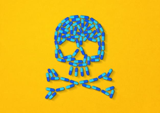 Череп из синих капсул, изолированных на желтом