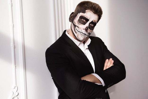 Skull make up portrait of young man. halloween face art