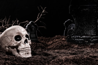 Skull on night cemetery with tombstones