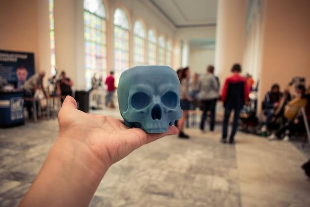 人間の手で3dプリンターで印刷された頭蓋骨。ぼやけた計画の裏側-人々。進歩的な現代の添加剤技術。コピースペース、テキスト用のスペース