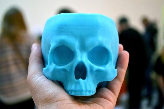 Череп напечатан на 3d-принтере в мужской руке. прогрессивные современные аддитивные технологии