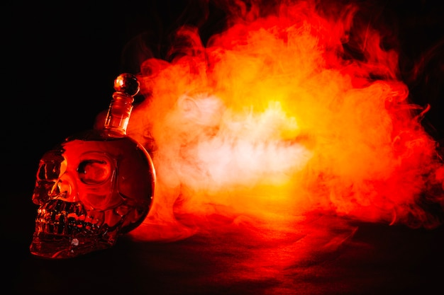 Skull-shaped bottle in red smoke