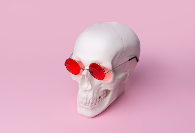 Skull in sunglasses on pastel pink table.