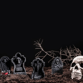 Skull and tombstones on night cemetery