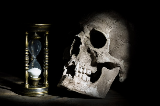 Skull and vintage hourglass on wooden under beam of light