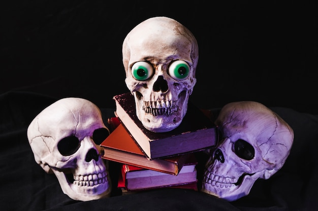 Skulls and books illuminated by purple light