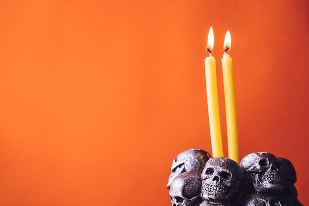 Skulls with candle burning on an orange color background. free space for text
