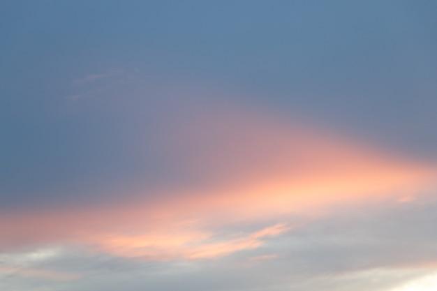 青とオレンジのグラデーションカラーの空と雲。夕暮れのカラフルな滑らかな空。