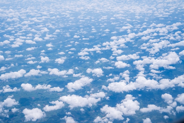 Sky clouds cape from aerial airplane shot of blue clouds. view flying above mountain