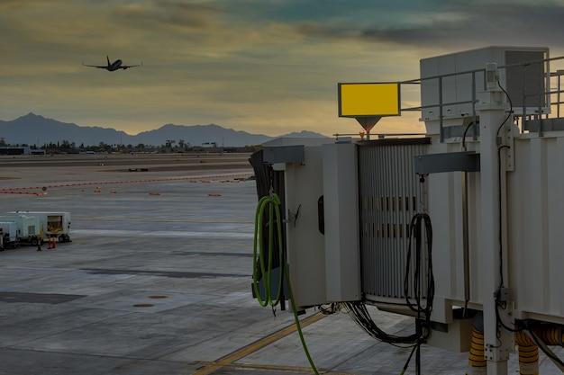 미국 애리조나 주 피닉스에서 공항을 연결하는 데 사용되는 탑승 다리에서 이륙하는 비행기와 일몰 스카이 하버 공항 공항