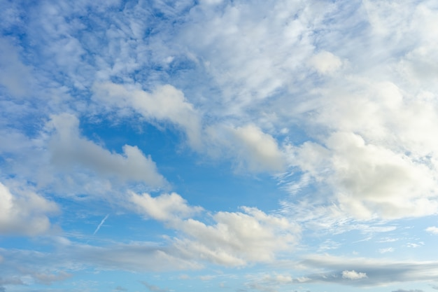 The sky is bright blue. there are clouds floating through. feel relax when looking.