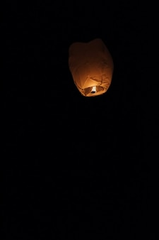 Sky lantern floating into the night sky at the festival in pingxi, the chinese text