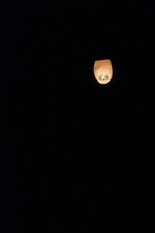 Sky lantern floating into the night sky at the festival in pingxi, the chinese