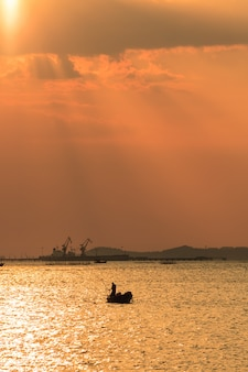 Sky orange and fisher man with cargo ship background