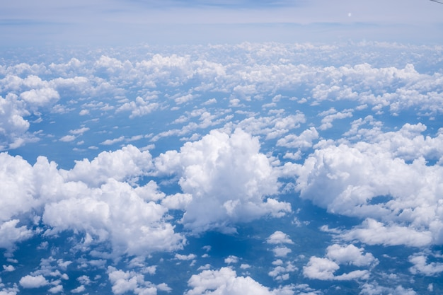 Sky scape cloudscape from aerial airplane shot of blue clouds. view flying above moutain from windows over loei, thailand.