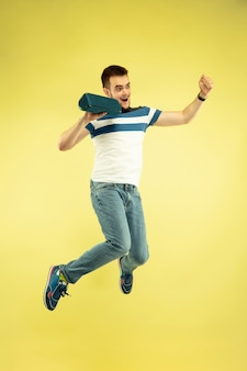 Sky sound. full length portrait of happy jumping man with gadgets on yellow background. modern tech, freedom of choices concept, emotions concept. using portable speaker like superhero in flight.