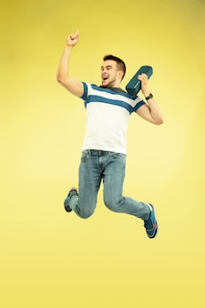 Sky sound. full length portrait of happy jumping man with gadgets on yellow background