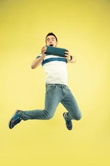 Suono del cielo. ritratto integrale dell'uomo che salta felice con i gadget su giallo.