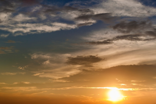 Sky at sunrise or sunset. white clouds lit by bright orange yellow sun on clear blue sky.
