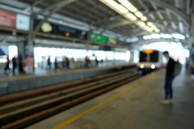 Sky train platform with travelers waiting blurred