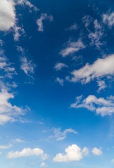 하루에 푹신한 파란색 흰색 구름과 수직 하늘