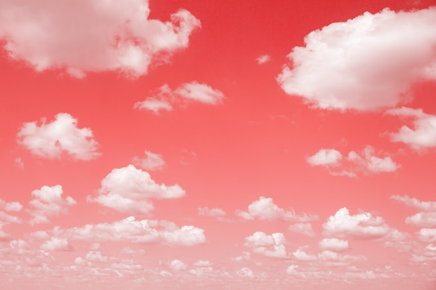 Sky with fluffy clouds. toned abstract in living coral color