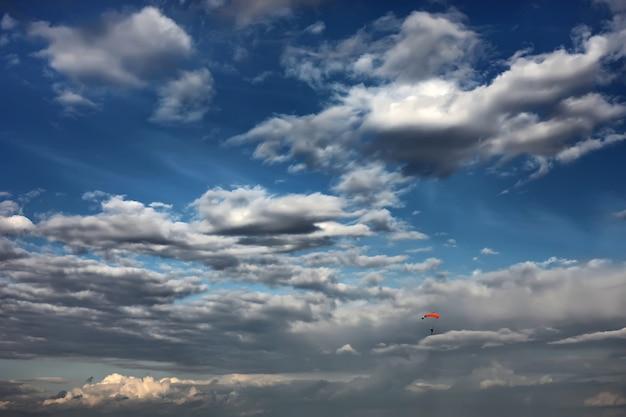 空のスカイダイバー。美しい雲の中で孤独なパラシュート。日当たりの良い夕焼け日の出空でカラフルなパラシュートでスカイダイバー。アクティブな趣味