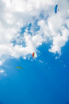 青い空にカラフルなパラシュートでスカイダイバー。アクティブな趣味