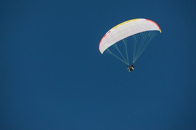 ジョージア州グダウリの青い空を背景にパラシュートの天蓋の下でスカイダイバー