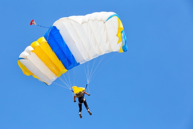 Skydiver under white dome of parachute