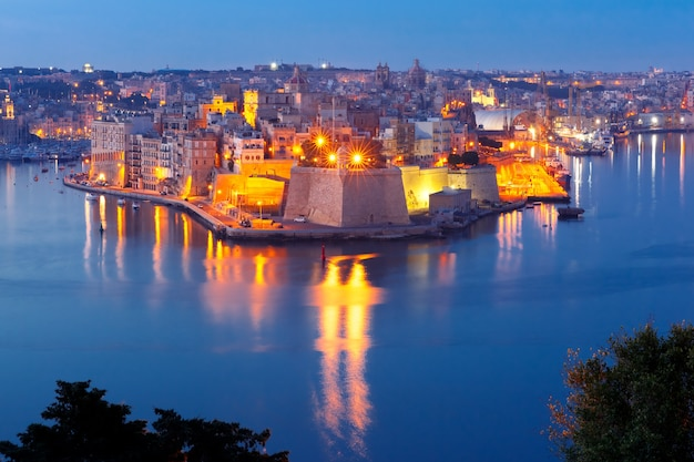 Skyline aerial view of ancient fort saint michael of senglea peninsula and the grand harbor as seen from valletta during morning blue hour, malta.