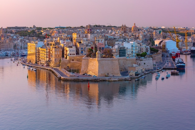 Skyline aerial view of ancient fort saint michael of senglea peninsula and the grand harbor as seen from valletta at sunrise, malta.