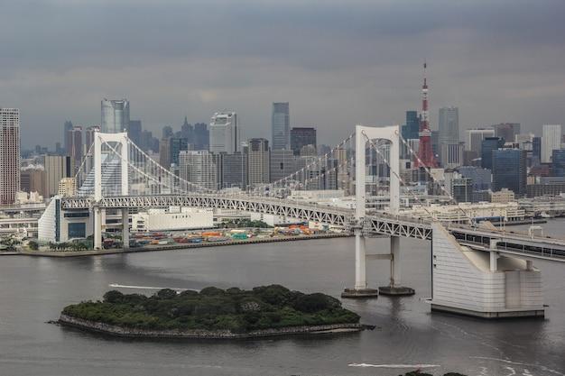 Orizzonte di un grattacielo della città di minato vicino a un ponte sospeso dell'arcobaleno a tokyo, japan