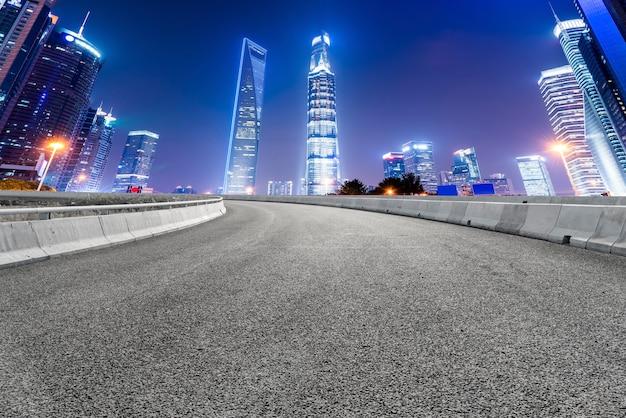 Горизонт асфальтового покрытия и ночной пейзаж архитектурного ландшафта шанхая