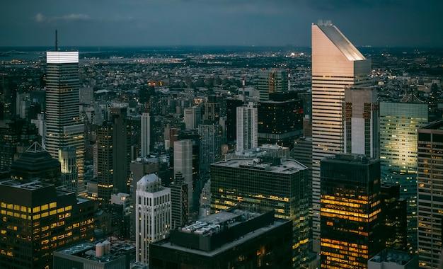 ニューヨーク市の高層ビルのライトで夜のマンハッタンのスカイライン