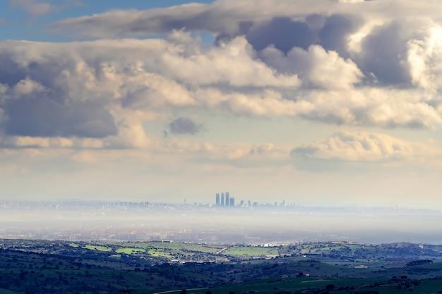 嵐を脅かす巨大な雲と霧の日のマドリードの街のスカイライン。スペイン。
