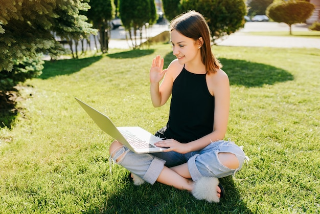 Портрет молодой привлекательной девушки, общение онлайн с помощью видео-звонка, skype разговор с друзьями, используя ноутбук, сидя на траве в парке.