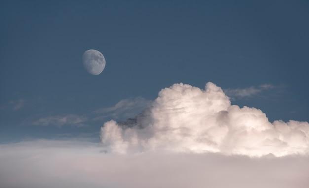 Skyscape、ふわふわの雲の上の青い空にほぼ満月