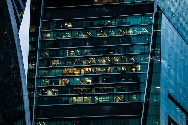 Skyscraper building with office windows, evening view with turned on lights
