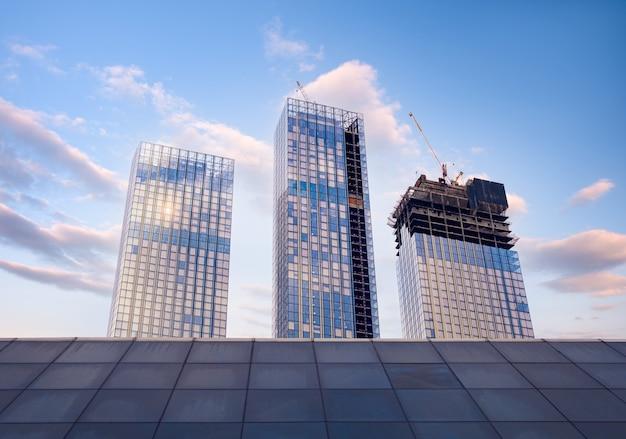 青い空に太陽光線が当たる明るい晴れた日の超高層ビルのガラスのファサード。経済、財政、事業開発活動の概念。ボトムアップビュー