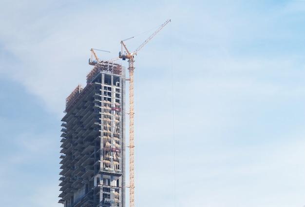 青空の背景にクレーンで建設中の超高層ビル
